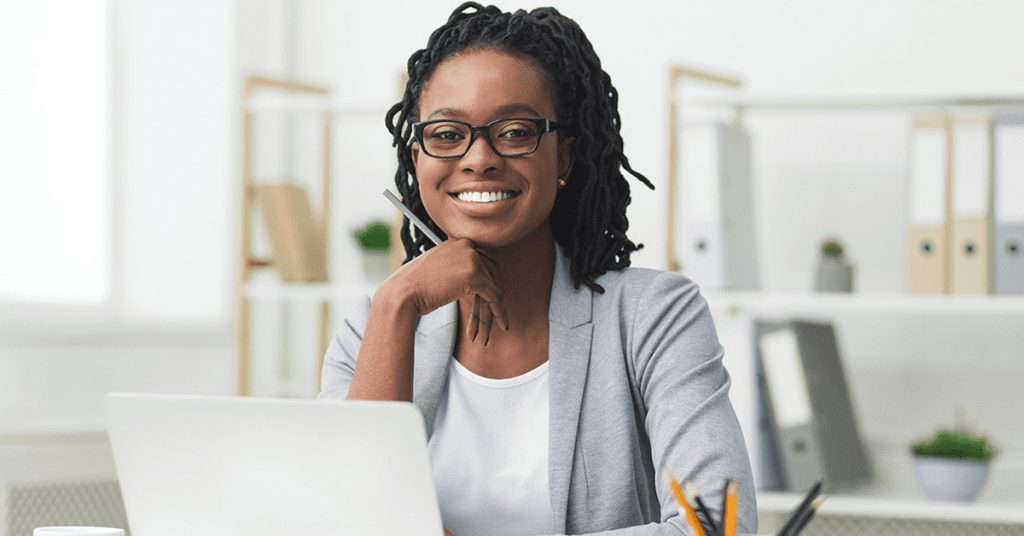 Business woman smiles as she works at her desk